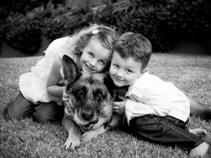 little boy and girl with german shepherd dog pet wearing white shirts sitting on grass