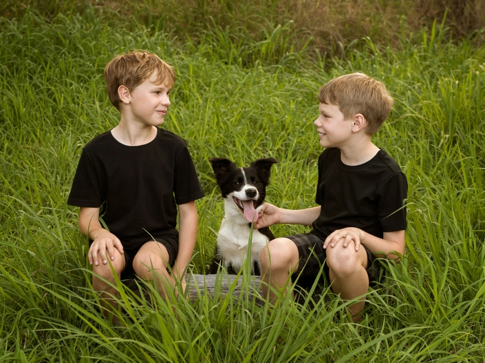 two young brothers and their black and white pet dog sitting in grass talking
