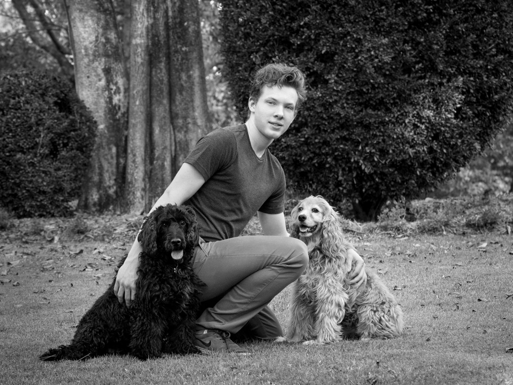 teenage boy with his two dogs sitting casually with arms around pets in park