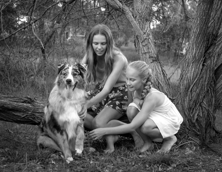 girls and their pet dog border collie with front paw up pose