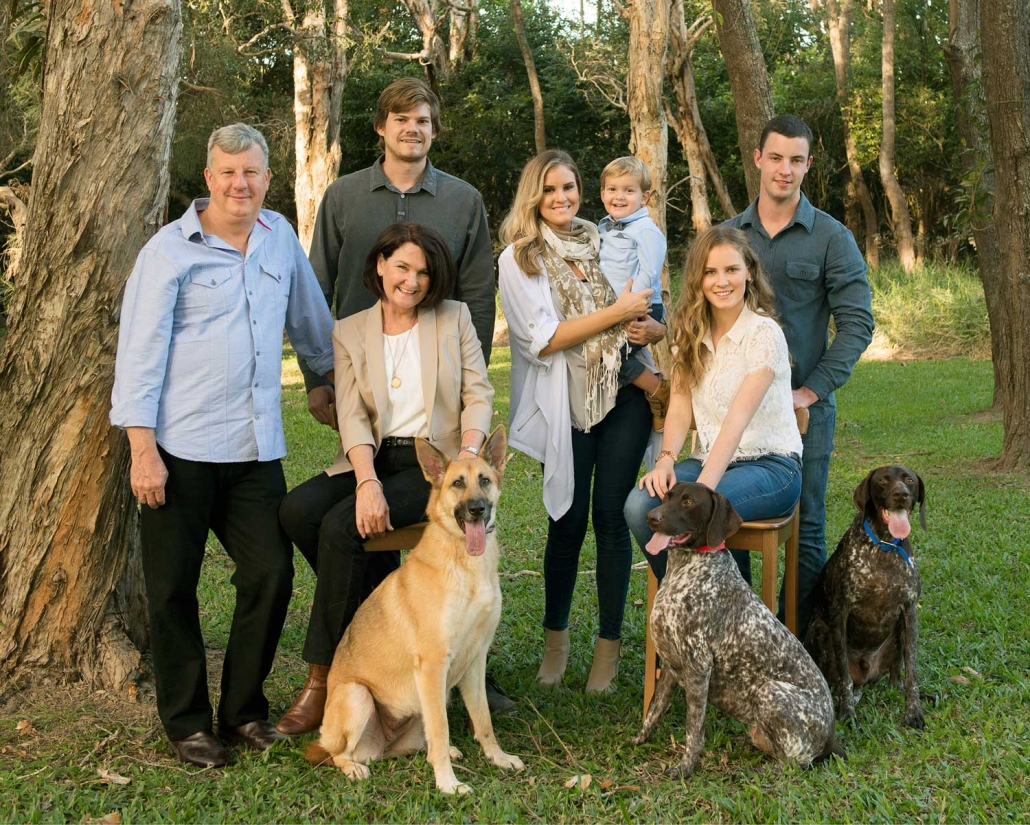 large multi generation family portrait with three dogs in front of australian native eucalyptus trees