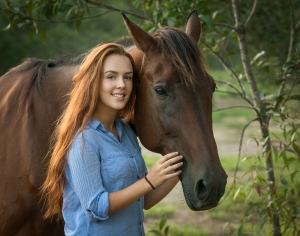 beautiful red hair girl standing with brown horse smiling