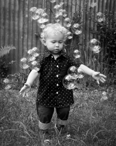 toddler boy playing in bubbles at kids photoshoot coorparoo