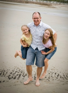 Dad holds two daughters on sandy beach having fun