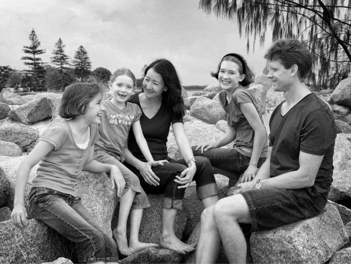 Mum and Dad on rocky beach with three kids laughing black and white image