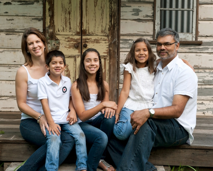 Family of 5 wears white shirts and jeans for family photography with rustic tin shed background
