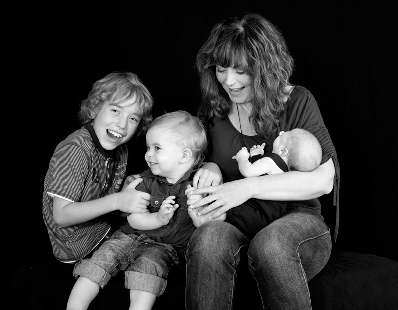Mother and her three children wearing casual clothing for photography session in studio