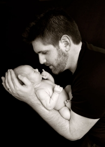 father holds newborn baby in arms close to face