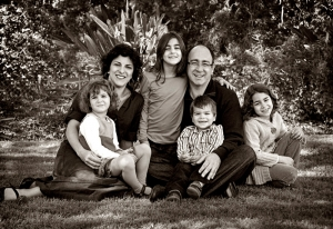 Family with four kids sitting in park on grass posing for family portrait with master photographer Frances Suter
