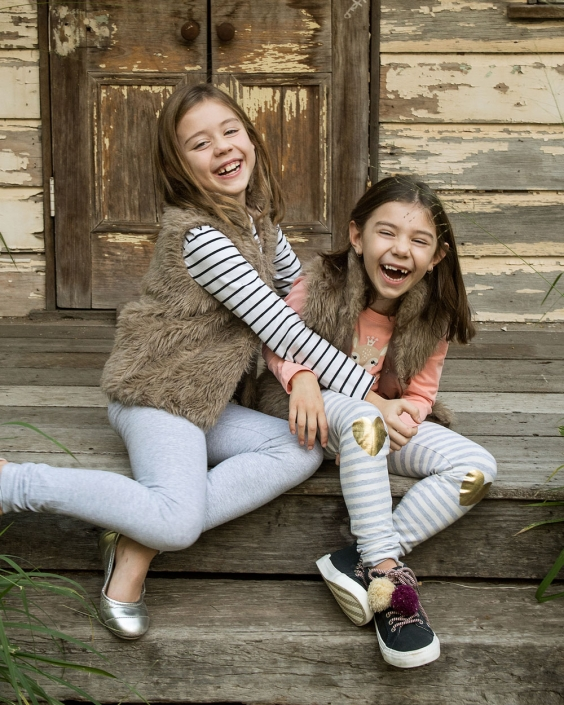 sisters laughing wearing winter clothing sitting in fornt of rustic tin shed