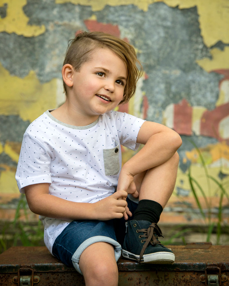 cool young boy sitting casual in front of vintage sign for children's portfolio photograph