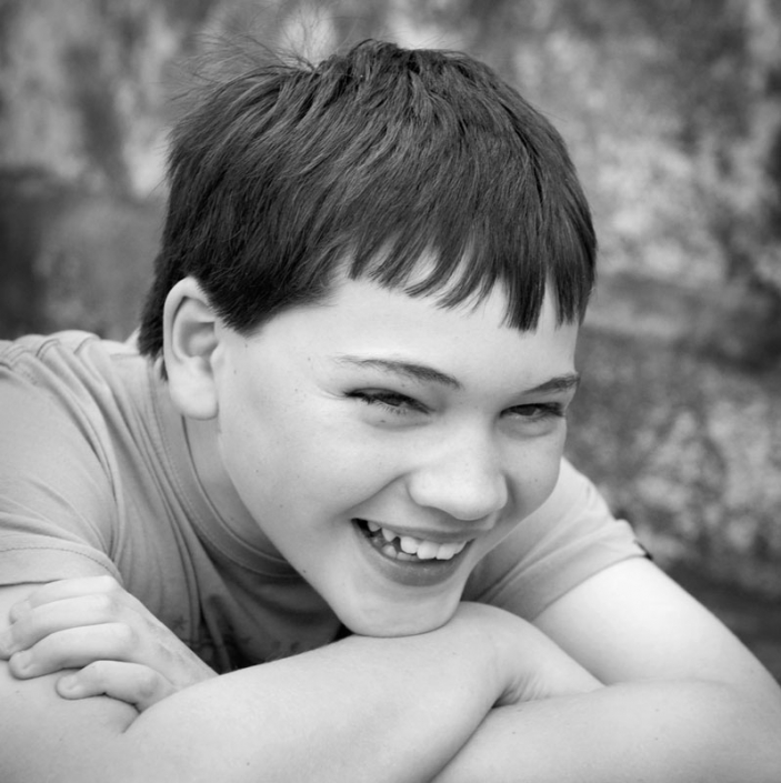 candid young teenage boy smiling naturally with arms folded in black and white