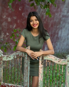 gorgeous young lady posing casually with antique gates in photography studio
