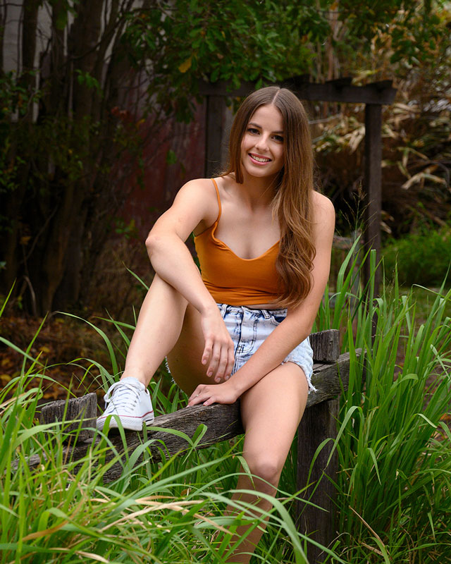 teenage girl sitting on country fence with fresh green long grass wearing denim shorts and singlet top