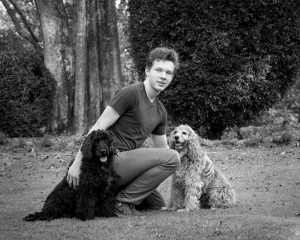 young man and two medium sized dog in new farm park