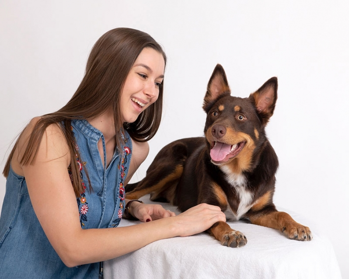 young lady wearing fashionable denim dress looks lovingly at kelpie dog white backdrop indoor studio lighting