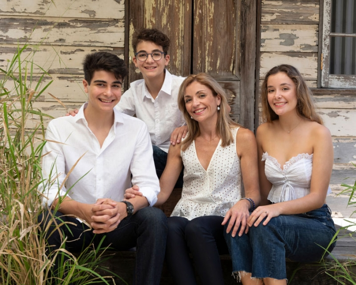 lovely family with Mother and two teenage sons and one teenage daughter wearing white and denim in front of rustic tin shed