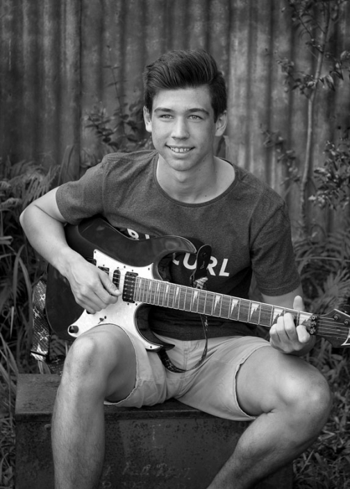 handsome teen young man plays his electric guitar while posing for black and white photograph outdoors
