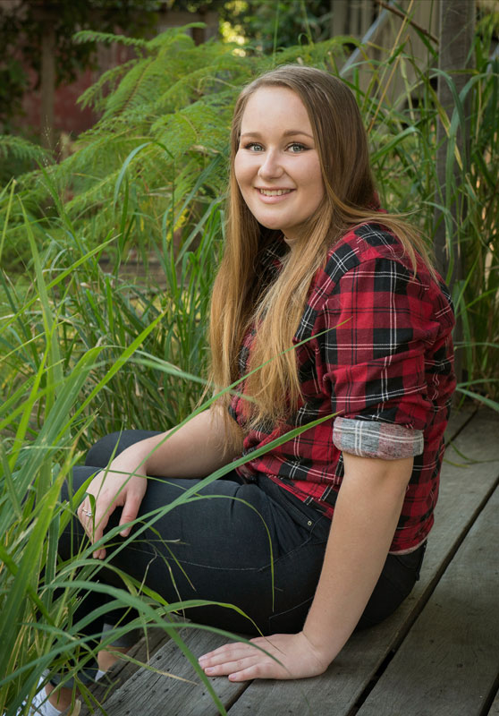 natural teen wearing red checker flannel shirt sits in garden on wooden shed