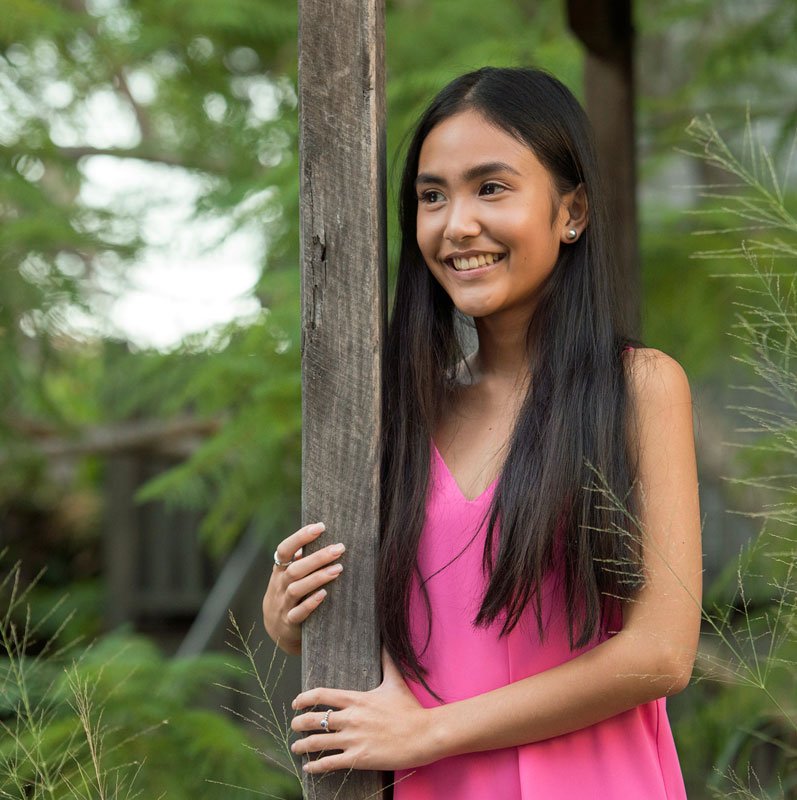 teen girl wearing bright pink dress looks happy leaning on homestead fence post