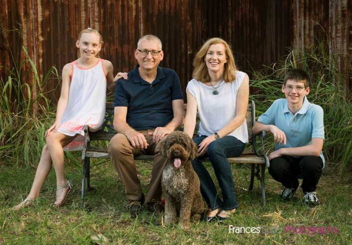 Family with two kids sitting on bench outside with brown dog casual portrait
