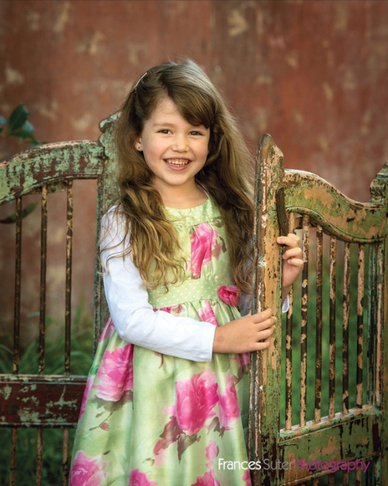 sweet little girl wearing floral dress smiles standing in antique gates
