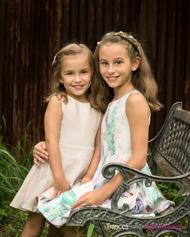 beautiful sisters sitting on garden chair for children's photography session