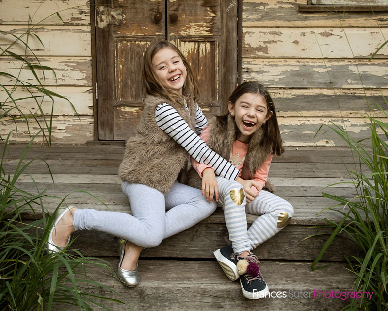 primary school aged sisters share a laugh and a hug wearing winter fashion outfits in front of rustic farm shed location