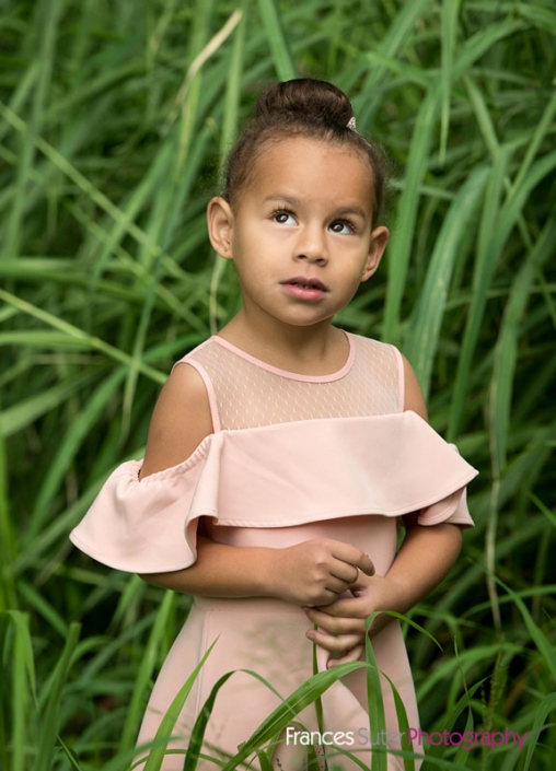 stunning little girl wearing pretty pink dress posing in long grass for photograph