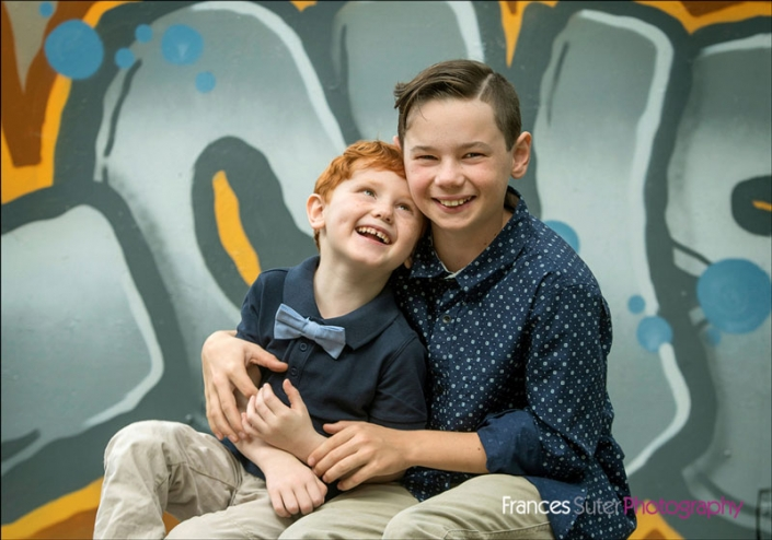 young brothers share a laugh sitting in front of graffiti wall wearing button up shirts and bow tie