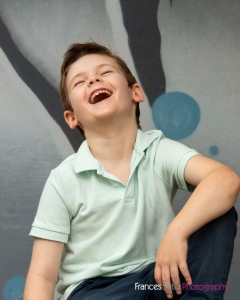 happy young boy wearing teal coloured t shirt laughs while posing for portrait in front of street art background