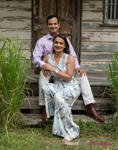 husband and wife sitting relaxed in front of farmhouse shed backdrop for photograph