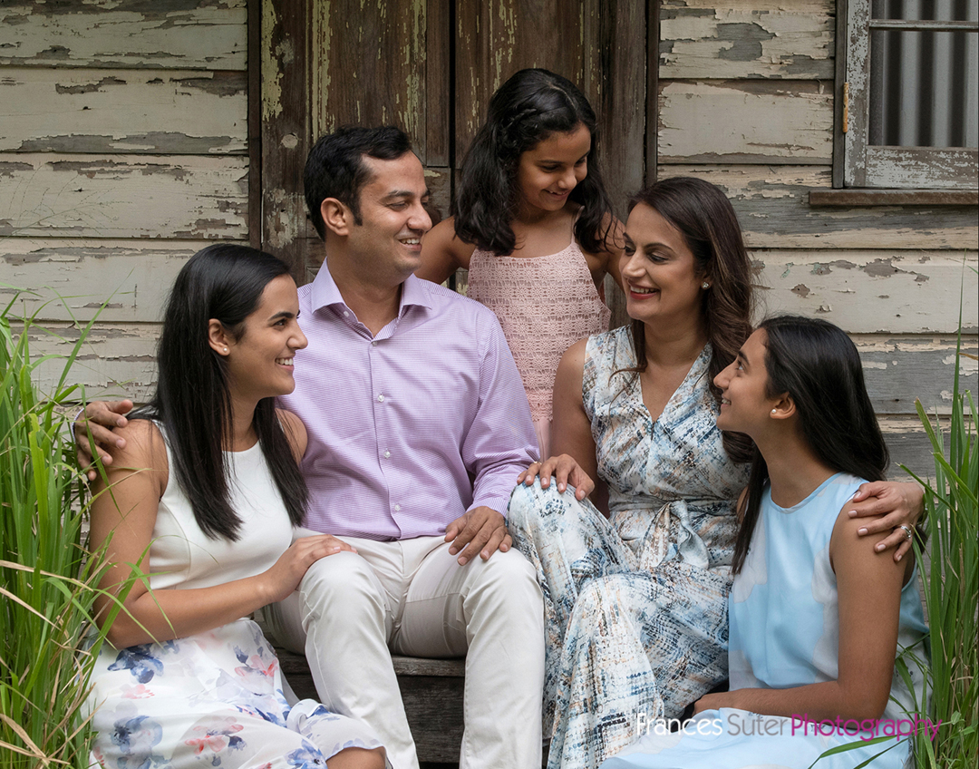 family wearing pastel coloured clothing posing for family portrait image in front of rustic tin shed backdrop