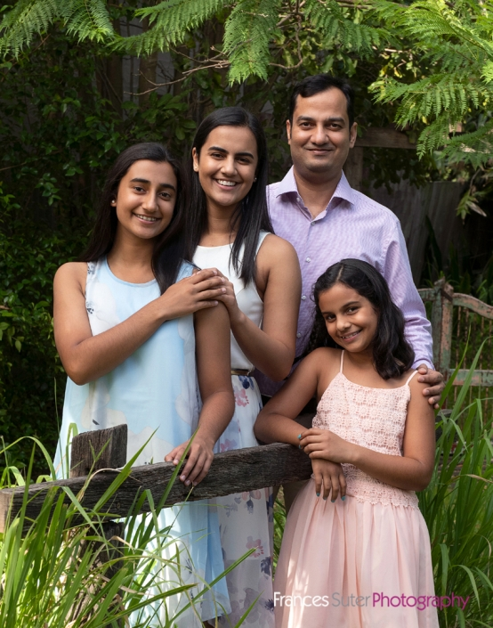 family photography in garden of dad with his three daughters wearing pastel coloured clothing