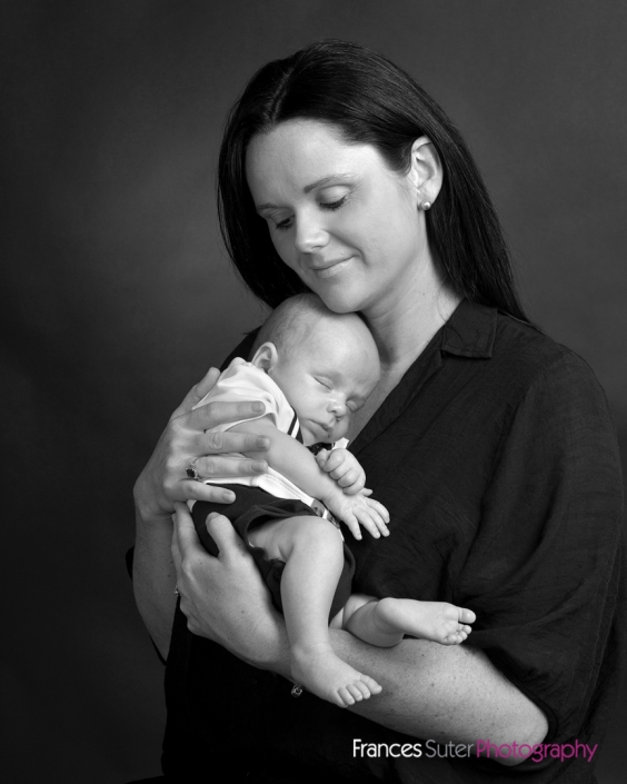 Mother holds her newborn son close to her chest photograph in black and white