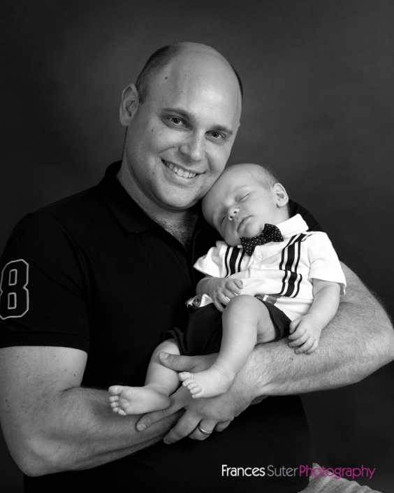 Proud Father smiles while holding his sleeping newborn son in his arms photograph in black and white