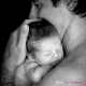 black and white image of father holding newborn baby