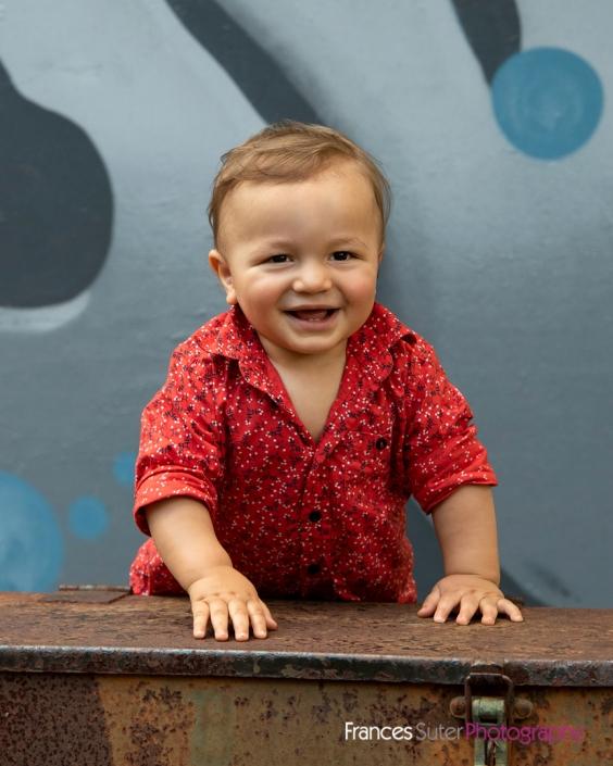 Toddler boy leans on large metal box laughing wearing red shirt