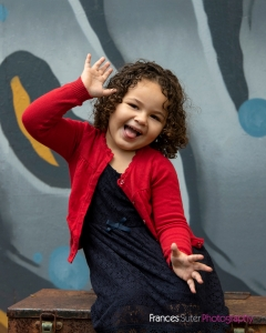 Young girl with curly hair laughing and striking a funny pose with hands in air wearing red cardigan and navy blue dress in front of graffiti wall