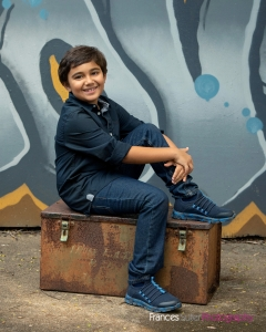 Young boy sits candidly on metal box in front of blue graffiti wall