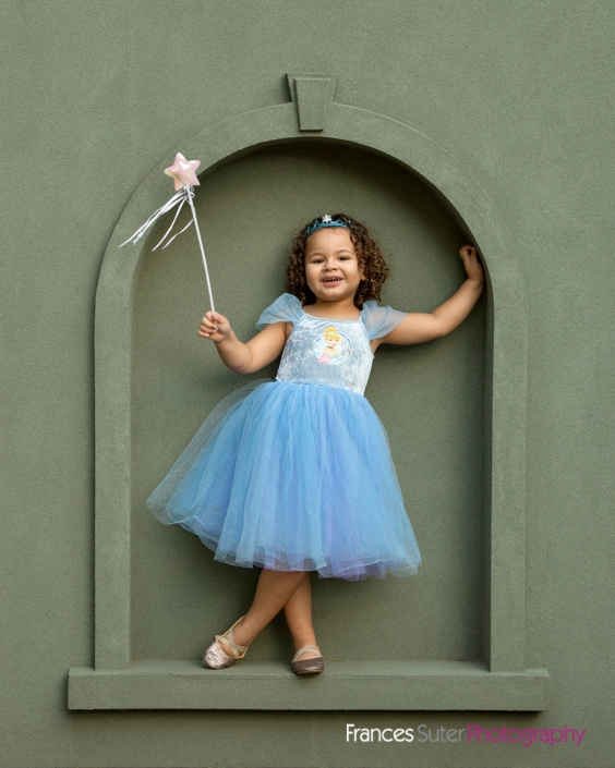 Little girl with curly hair wearing blue princess costume with crown and fairy wand