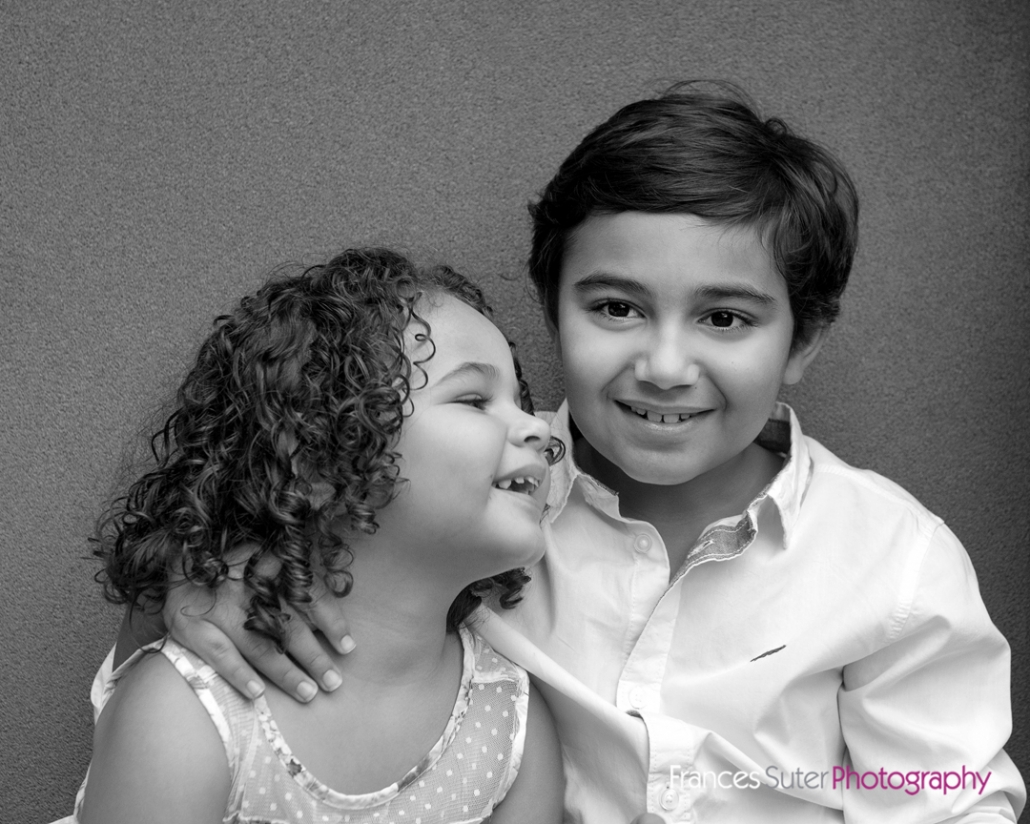 black and white image of young brother and sister posing happily in outdoor photography studio Brisbane