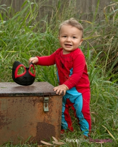 toddler wearing Spiderman costume holds mask and leans on metal box to stand up