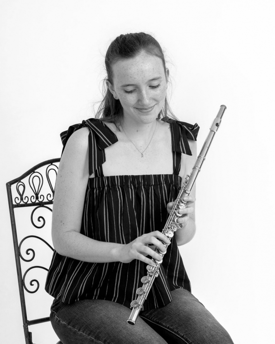 Young musician holds instrument for headshot photograph
