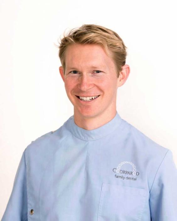 Dentist wears blue uniform for corporate headshot brisbane