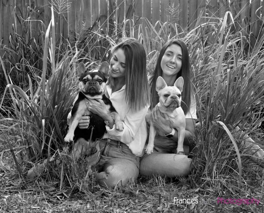 Two ladies sit in outdoor grass setting holding two french bulldogs for pet photoshoot